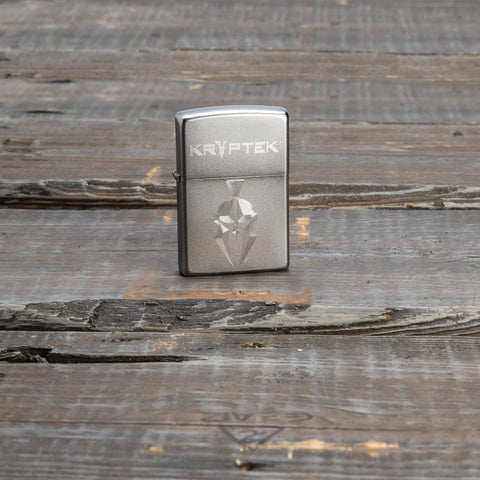 Lifestyle image of Kryptek Satin Chrome Windproof Lighter standing on a wooden surface