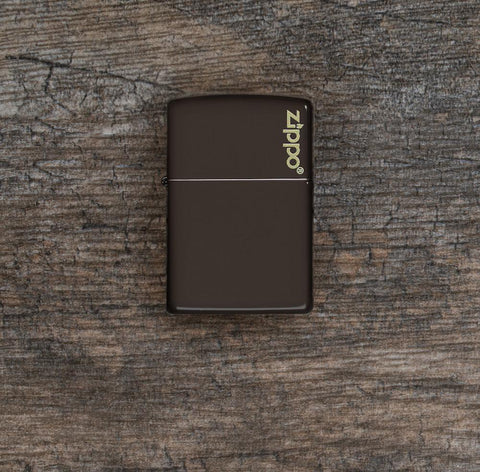 Lifestyle image of Brown Zippo Logo Windproof Lighter laying flat on a wooden background