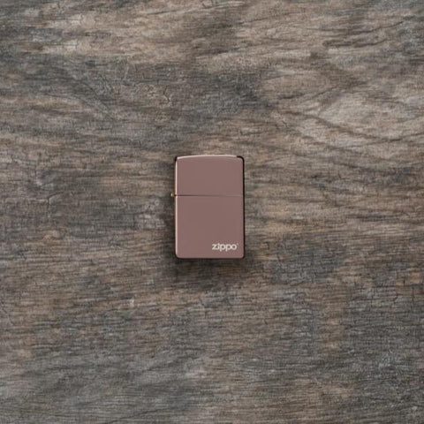 Lifestyle image of High Polish Rose Gold Zippo Logo laying flat on a wooden surface