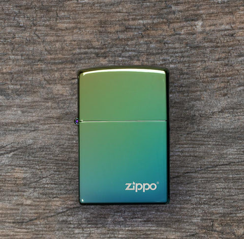 Lifestyle image of High Polish Teal Zippo Logo Windproof Lighter laying flat on a wooden surface