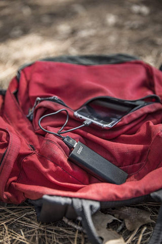 Black HeatBank 3 Rechargeable Hand Warmer laying on a backpack charging phone in the woods