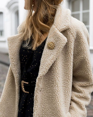 Stunning outfit that is accented with a pretty sunSemi-precious Goldtone brooch pin on a beige coat. The model also had blond hair and Yellow-gold Earrings