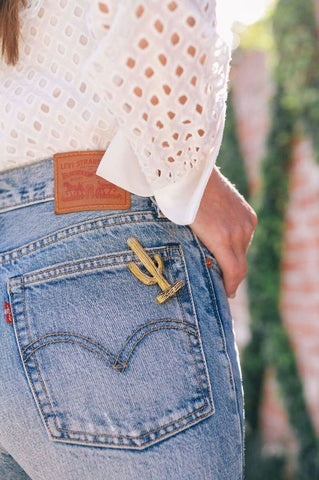 Verry pretty girl from behind with a gold-toned cactus charms and badge on the pocket of her jeans