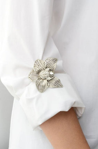 A white blouse with a flower brooch as a bracelet