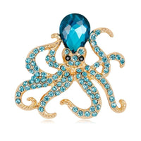 Gold-tone and blue octopus brooch vintage on a white background
