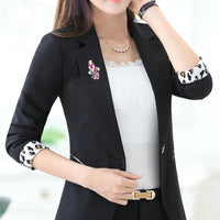 A model with a black blazer, a black bracelet, a gold necklace, and a gold belt. She also has an antique style Phoenix bird brooch as an extra jewellery.