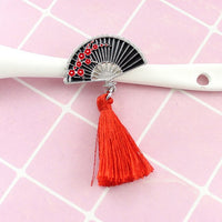 Fan inspired red brooch resting on a pink background