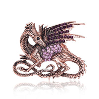 Dazzling, sparkling and retro vintage-inspired dragon brooch with pink and purple clear crystal. Black inspired gemstones are sitting in its eyes. It is resting on a white background