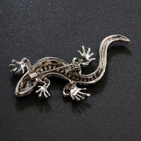 A picture of a silver lizard brooch revealing its pin, and motifs