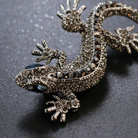 A macro picture of a silver lizard brooch perfect for a wedding with its silver-tone