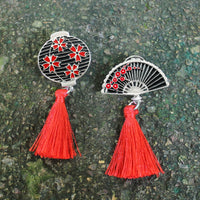 Two vintage-inspired Japanese charms with red and silver-toned.