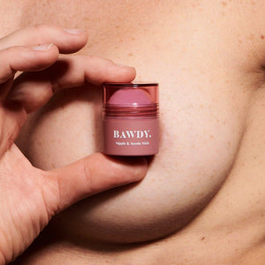 Woman holding pink Bawdy Beauty nipple and aerola stick in front of her nipple