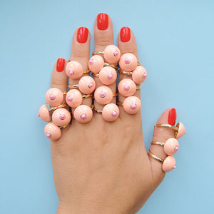 Woman's hand showing fingers covered in pink boob-shaped rings