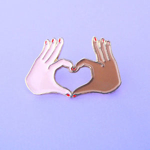 Enamel pin with two hands forming a love heart