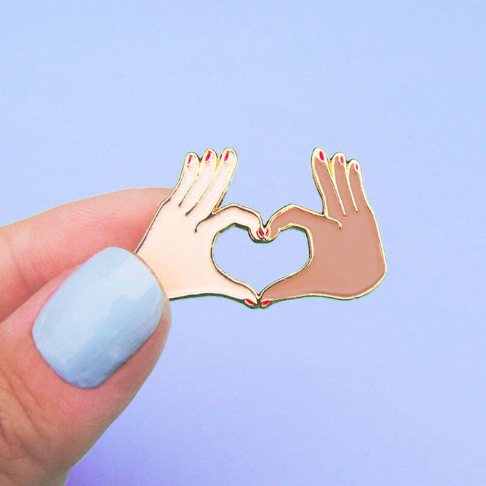 Fingers holding an enamel pin with two hands forming a love heart
