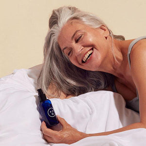 Smiling mature woman holding a blue bottle of Dame organic aloe vera lubricant