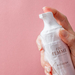 Woman's hand holding a bottle of Fig Femme Restore foaming daily wash for delicate intimate care