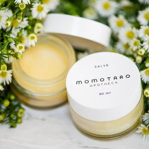 Pot of Momotaro Apotheca Salve organic vulva balm on a bed of fresh white flowers