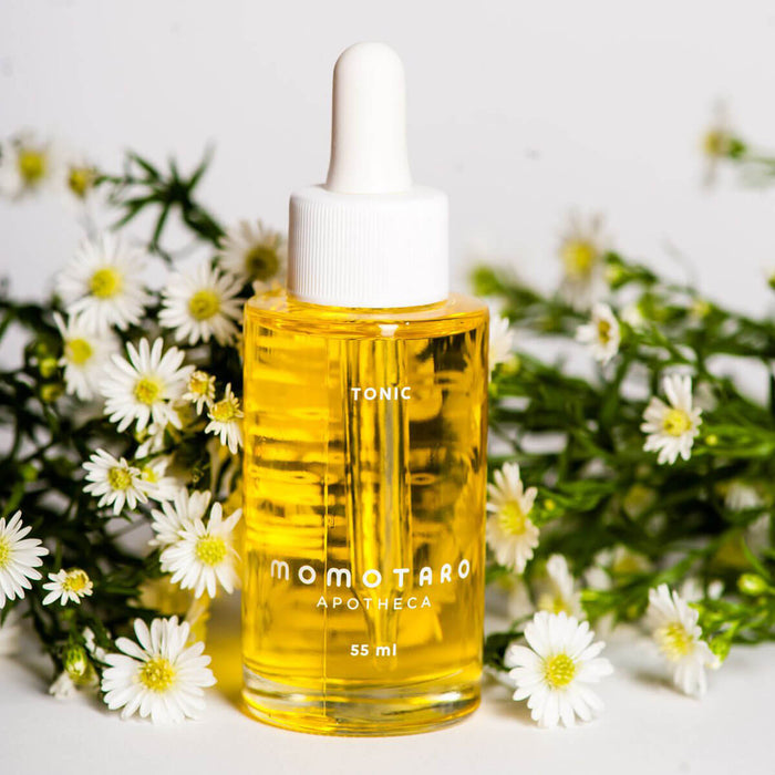 Bottle of Momotaro Apotheca yellow Organic Tonic in glass bottle for vaginal wellness with fresh daisies