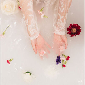 Woman in bath with white water and flowers