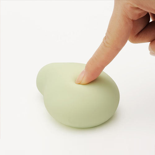 Woman's finger pushing on a soft squishy green Midori clitoral vibrator by Tenga Iroha