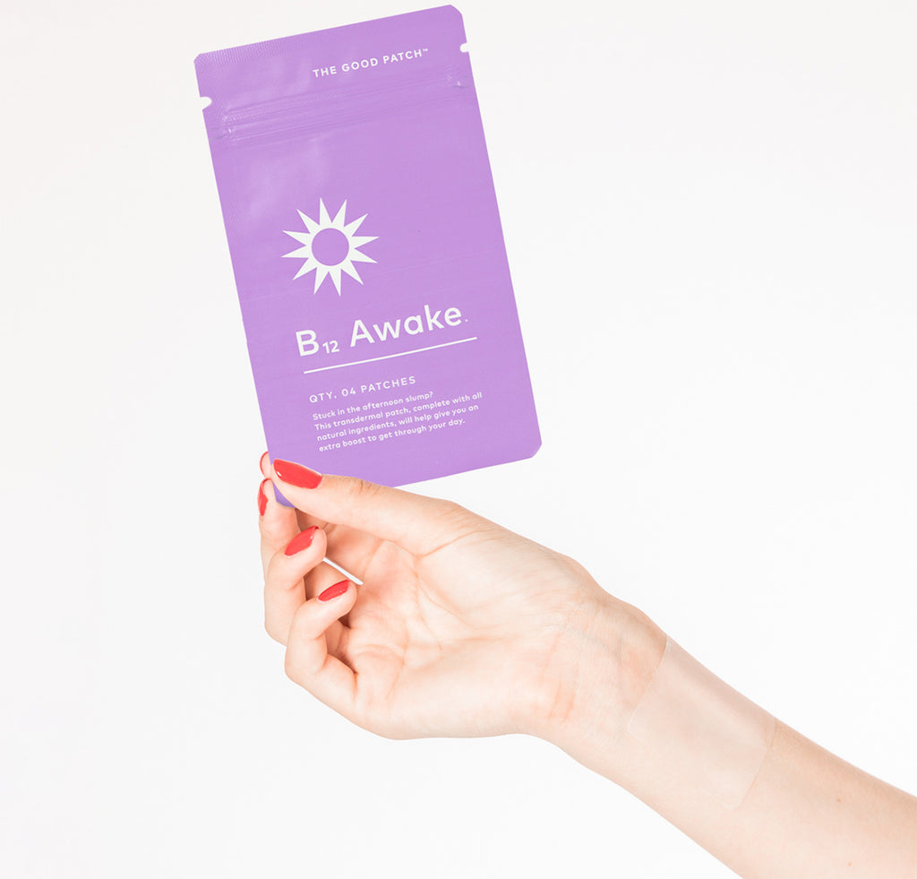 Woman's hand holding up purple plant-based wellness patch with B12 vitamins