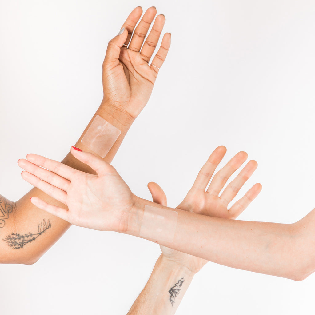 Three bare arms showing off plant-based wellness patches stuck on their wrists