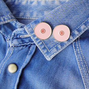 Two pink boob-shaped pins on a denim shirt's collar