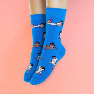 Woman's feet wearing blue socks printed with girls