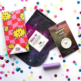 Chocolate tablet, cosmetics and small purple bullet vibrator on a white background with colourful confettis