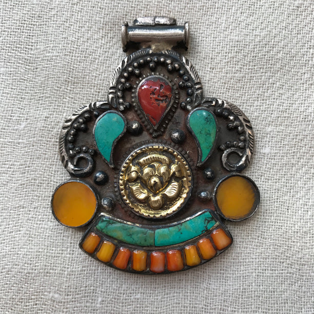 Antique looking silver and brass pendant set with amber, turquoise, and coral