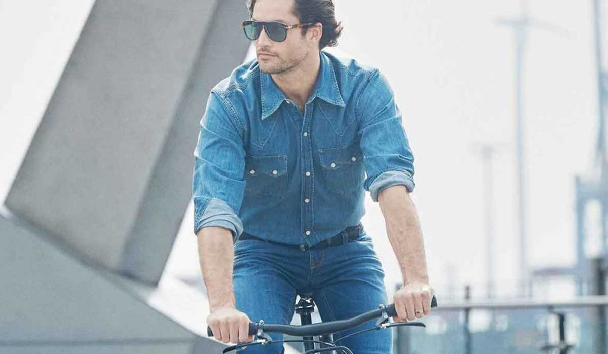 Image of man riding a commuter bike in the city wearing Alberto pants
