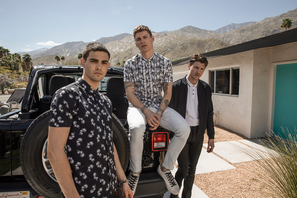 Image of three men posing in front of the back of a jeep, all of them wearing John Varvatos