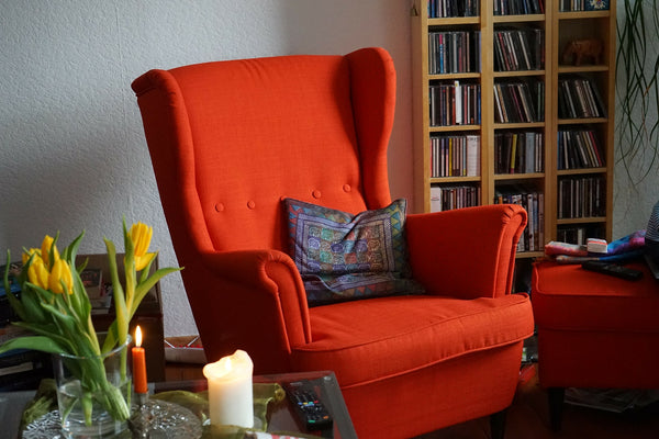 Armchair beside window with books and fresh flowers