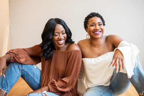 Two Black women hanging out with big smiles on their faces. This is an image for illustrating mentoring relationships.