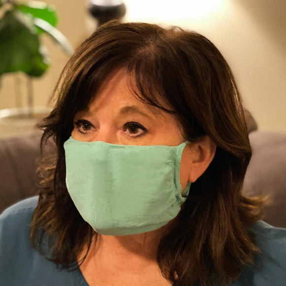30X Mask, scrub green ear loop mask, worn by a woman in scrubs