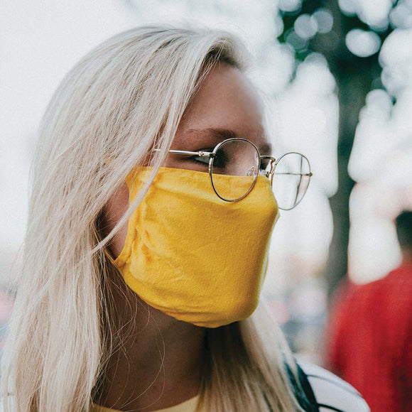 30X Mask, Mellow Yellow ear loop mask, worn by a young woman in sunglasses