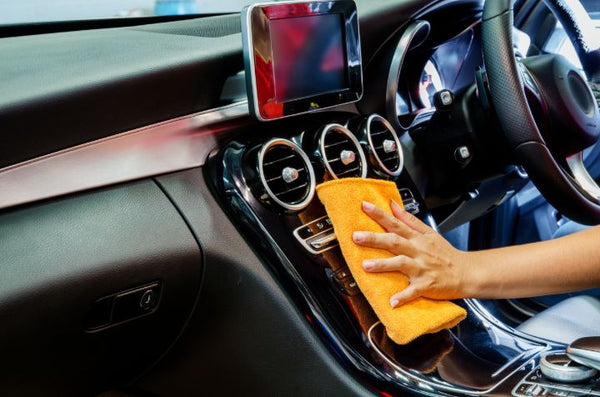 Person cleaning interior car controls with a microfiber cloth