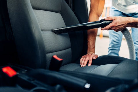Person cleaning car interior with a vacuum