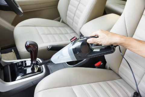 Portable car vacuum being used in the front of a car