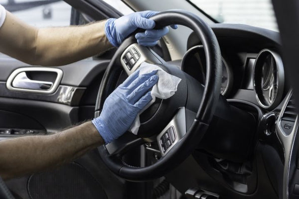 Person sanitizing a steering wheel with a cleaning wipe