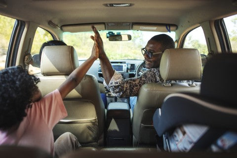 Family high fiveing at the beginning of their road trip