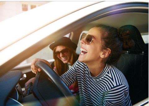 Two girls laughing as they are in a car road tripping.
