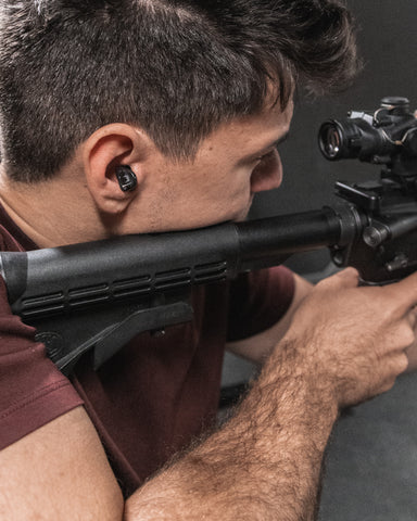 Man shooting rifle with tactical hearing device in ear
