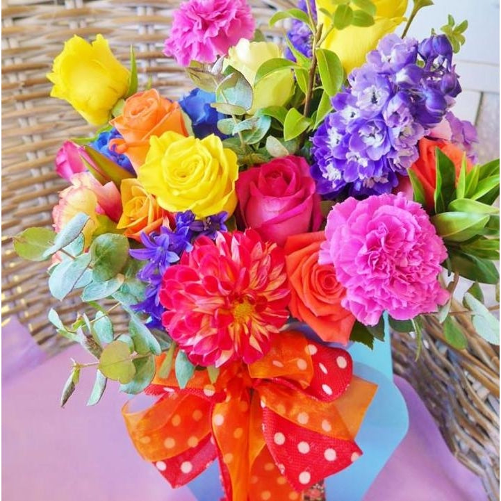 "Jellybean. A vibrant and funky arrangement of bright seasonal flowers arranged in our new modern style.  Loose formed but carefully constructed to envoke a ""just picked from the garden"" look.  Delivered in our new bloombox and finished with a big bright bow."