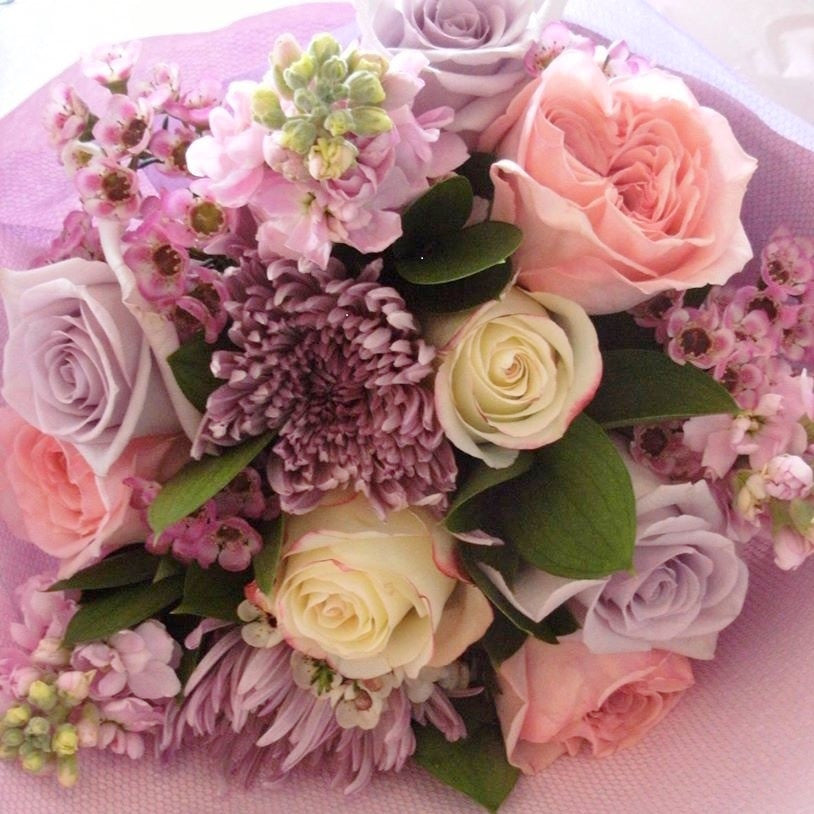 Mauve Mist.  Soft tones of purples, pinks and creams.  A wistful arrangement of roses, chrysanthemums and stocks with wax-flower and foliage fillers.  Wrapped in layered pink embossed paper with a fabric outer and complimenting ribbons.