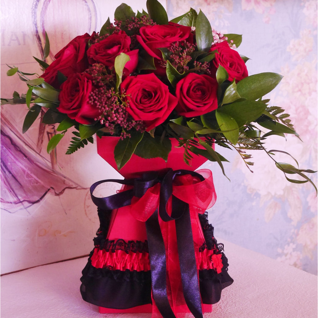 Moulin Rouge. A dozen red roses styled with complementing foliage, hand tied and arranged in a handmade lace trimmed vase box.