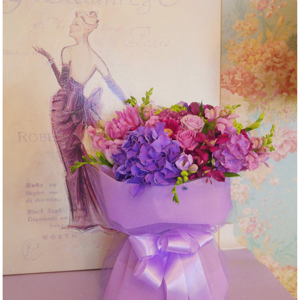 Luscious Lilac Jewel.  A beautiful coloured flower arrangement of lilac, deep cerise and mauve, a true jewel mix. Delivered in a water box and stylishly finished with a complimentary lilac wrap and ribbon.