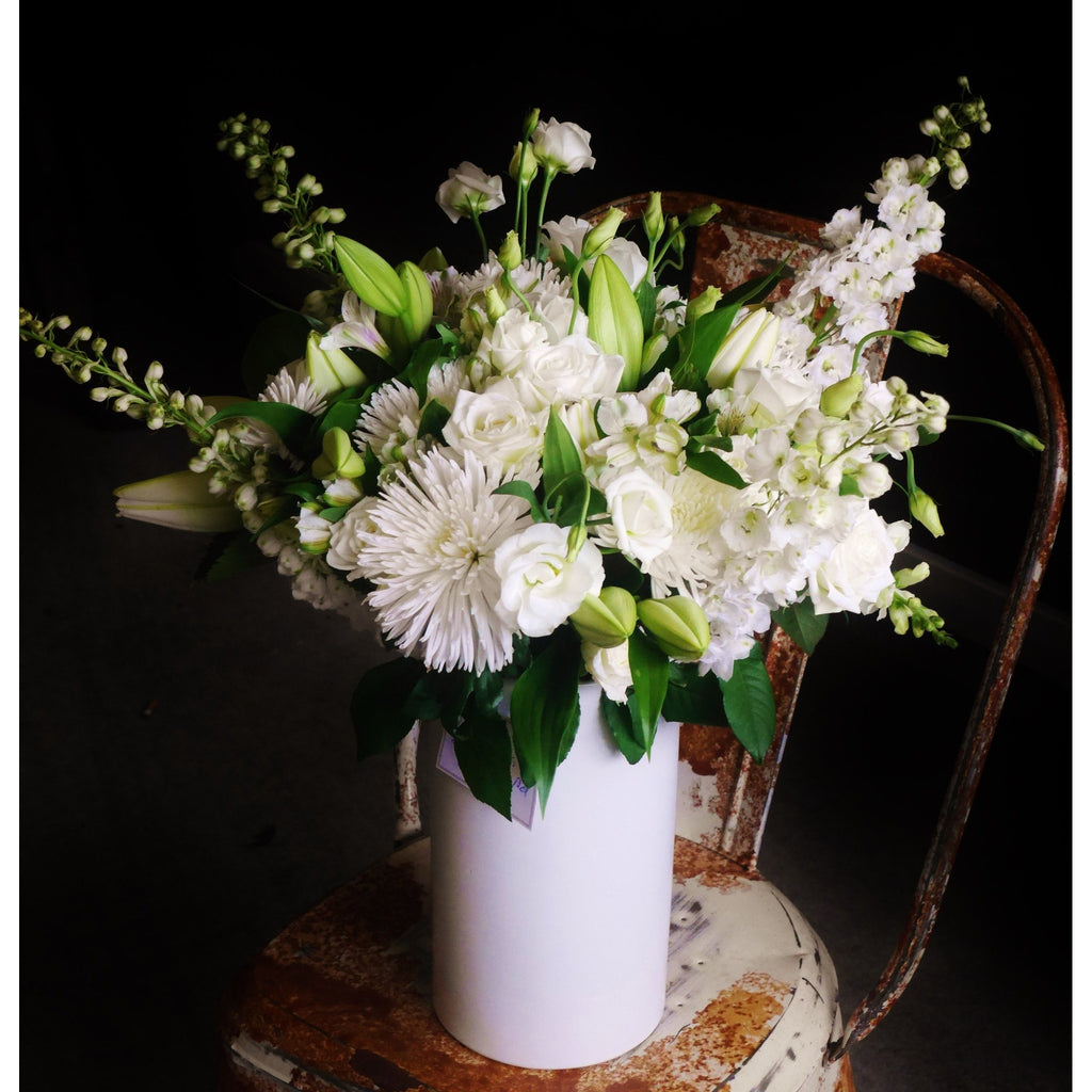 Classical elegance with a New York Loft vibe (white on white on white!). A ceramic white vase brimming with whites, creams and a touch of green. Overflowing with lilies, chrysanthemums, roses, snapdragons and delphinium all arranged in a relaxed style.