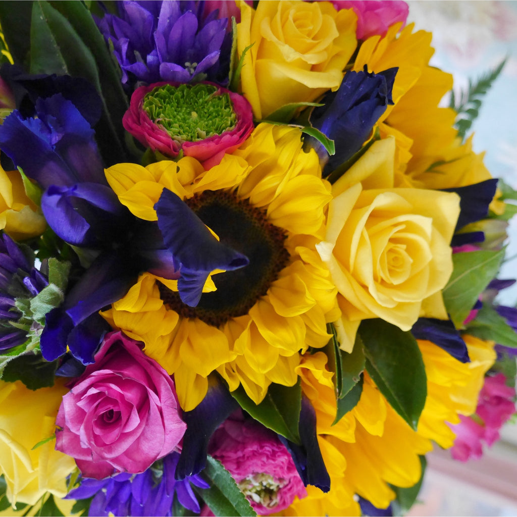 Beau  Soliel or Beautiful Sun - Round form Bouquet.   A sunny mix of seasonal flowers that will brighten anyone's day.